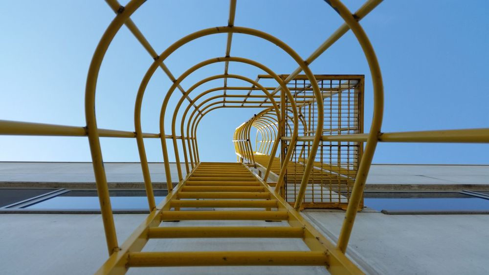 Safety metal ladder to the roof and blue sky, iron staircase Architecture Blue Built Structure Diminishing Perspective Directly Below Empty Engineering Escape Evacuation Geometric Shape Ladder Low Angle View Modern Narrow Outdoors Railing Sky Stairs Sunny The Way Forward Vanishing Point Walkway Yellow