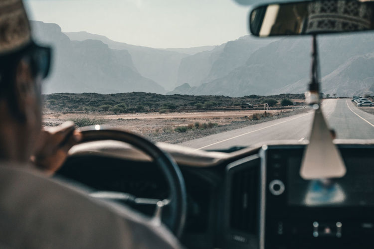 Cropped image of man driving car on highway against mountains