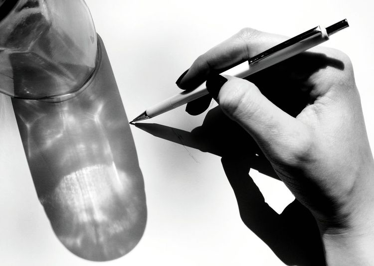 Cropped hand of woman drawing in book