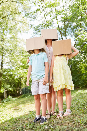 Mother and children covering faces with cardboard boxes at park
