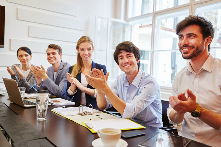 Smiling business people clapping at office