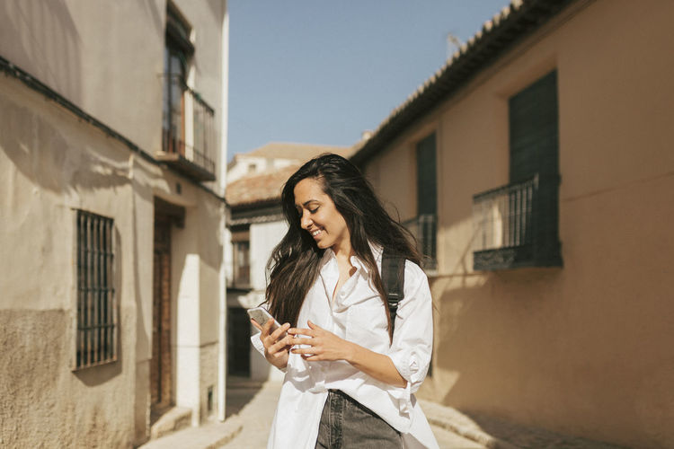 Young woman using phone while standing on building