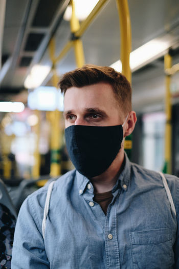 Close-up of man wearing mask in train