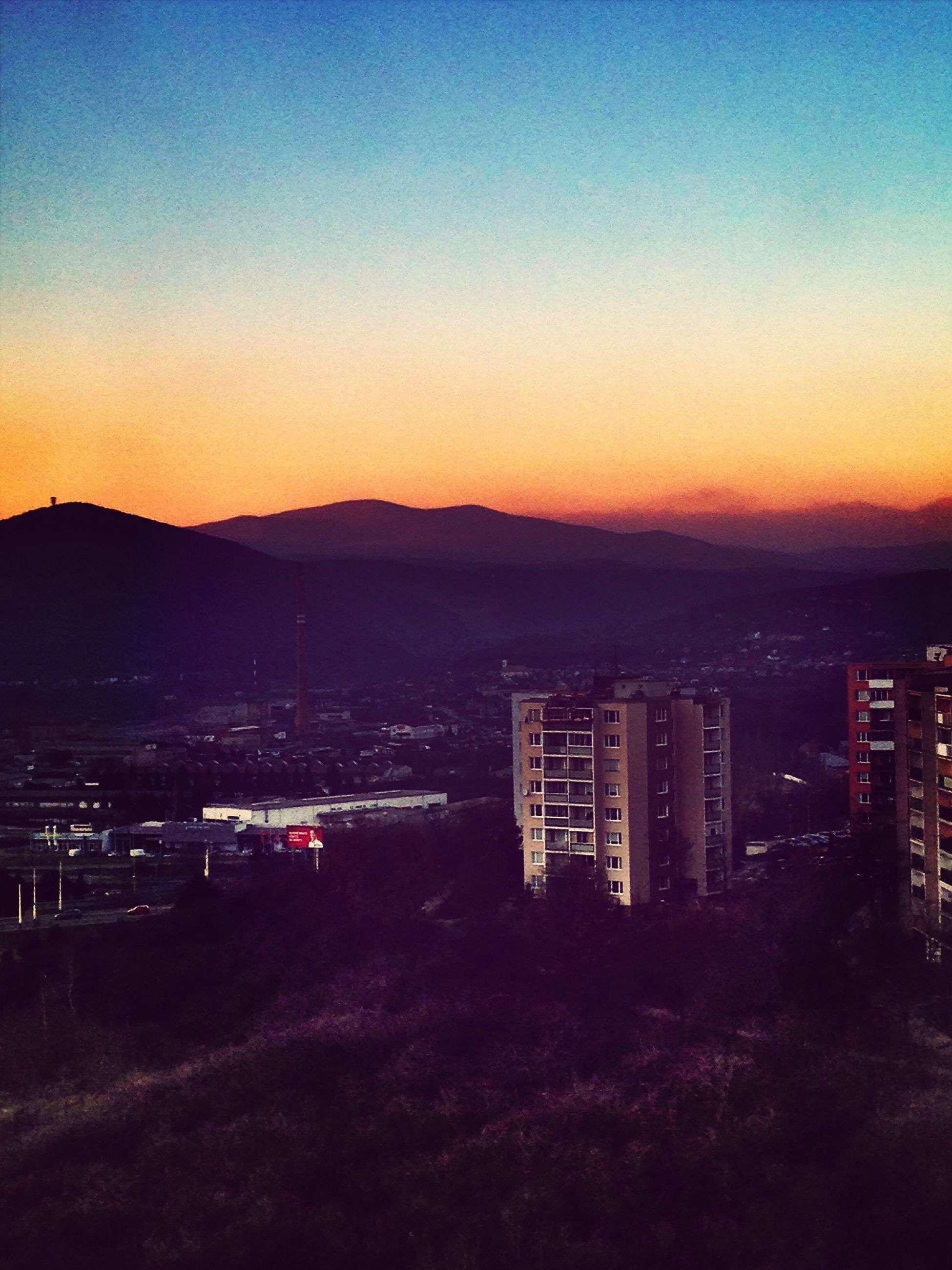 mountain, sunset, clear sky, copy space, building exterior, city, architecture, built structure, mountain range, cityscape, orange color, dusk, illuminated, scenics, landscape, tranquility, outdoors, high angle view, tranquil scene, beauty in nature
