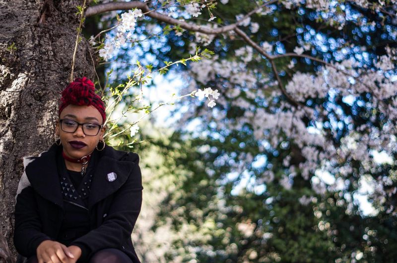 Low Angle Portrait Of Punk Woman Sitting Against Cherry Blossom Tree