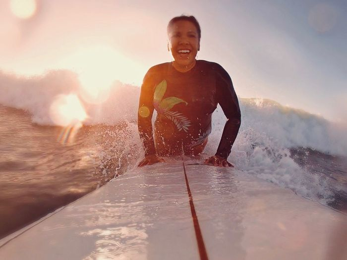 Portrait Of Smiling Woman Surfing On Sea During Sunset