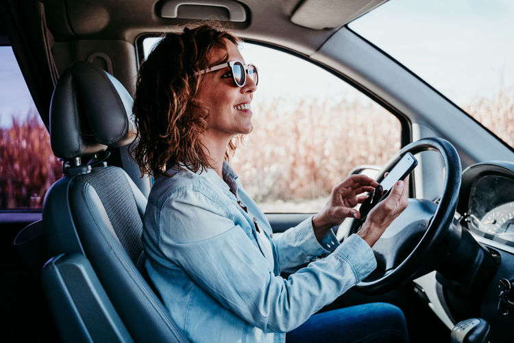 Side view of smiling woman driving car