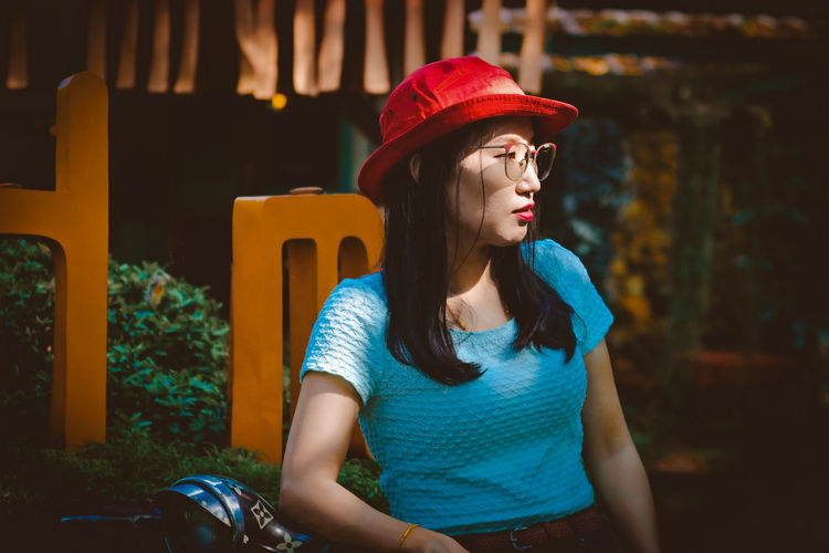 Woman wearing hat and eyeglasses standing outdoors