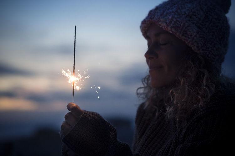 Woman holding sparkler against sky during dusk