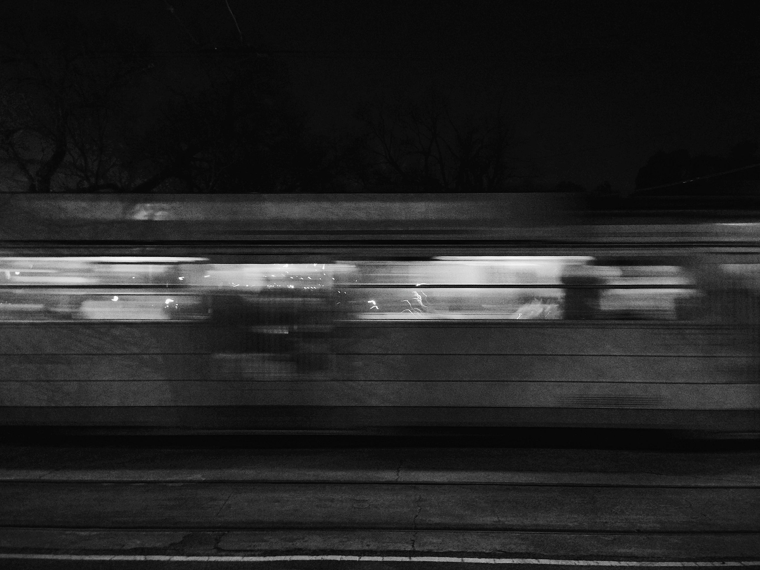 night, transportation, illuminated, railroad track, rail transportation, railroad station platform, railroad station, public transportation, mode of transport, dark, blurred motion, train - vehicle, street, motion, built structure, on the move, road, outdoors