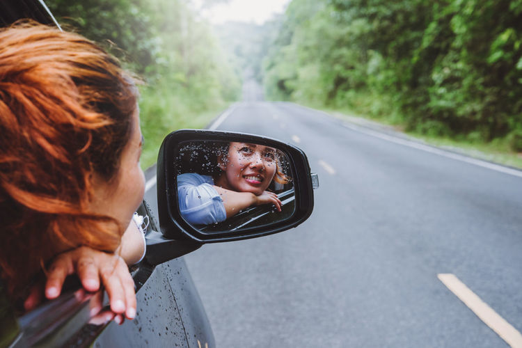 Reflection of woman in car side-view mirror on road