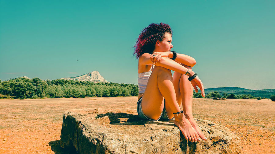 Young woman looking away while sitting on land against clear sky
