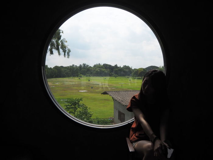 Field Seen Through Glass Window With Woman Sitting