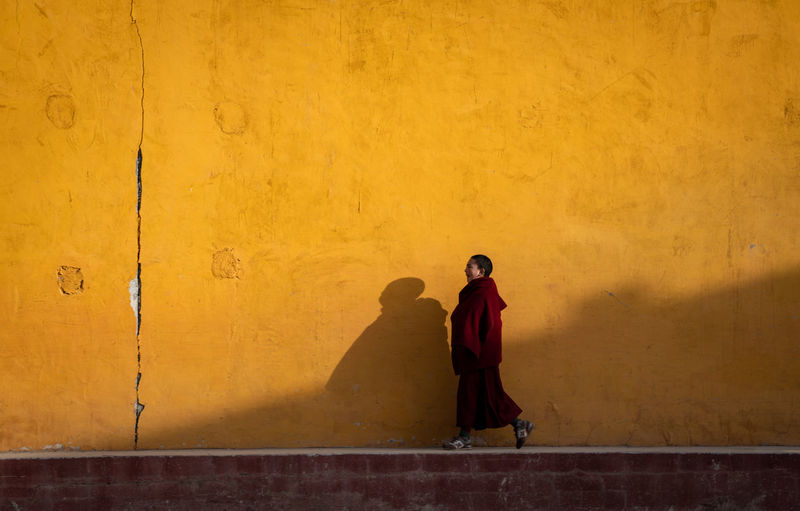 Man and woman standing against yellow wall