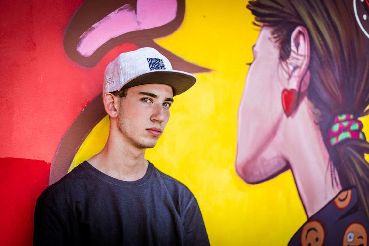 Portrait of young man against graffiti wall