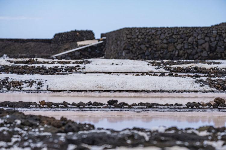 Surface level of rocks on beach against clear sky