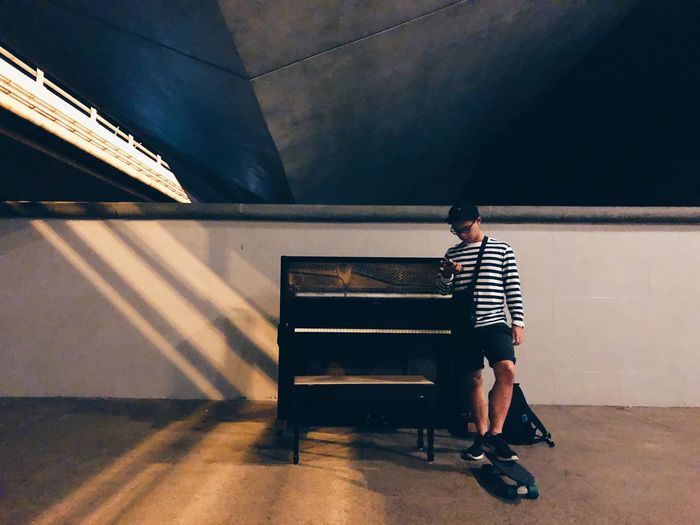 Full length of man using phone while standing with skateboard by piano