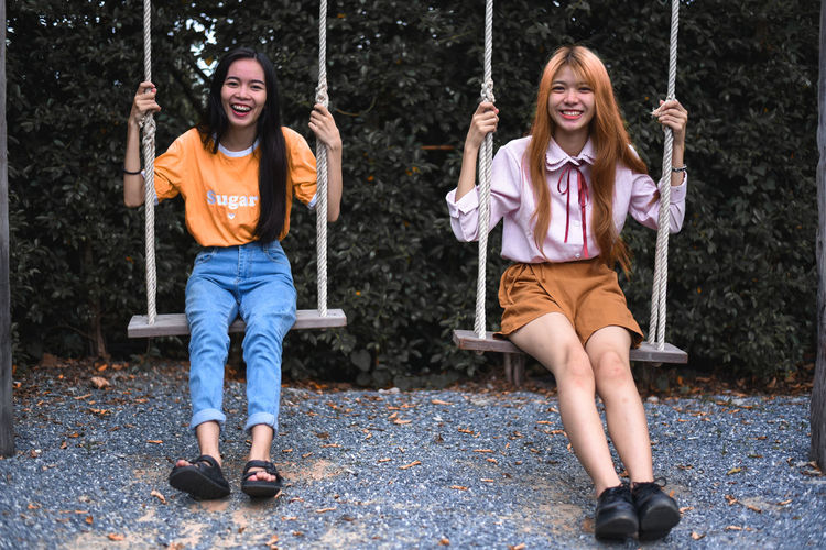Portrait of happy sisters swinging in park