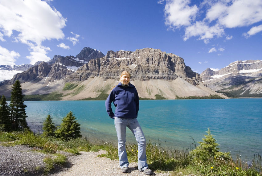 young woman in front of the bow lake - in the rockies, Canada Banff National Park  Beauty In Nature Bow Lake Canada Canadian Rockies  Casual Clothing Front View Full Length Hiking Lake Lake View Lakeshore Mountain Mountain Range Mountains Nature One Young Woman Only Rocky Mountains Scenics Vacations Wanderlust Water Woman Young Woman Young Women