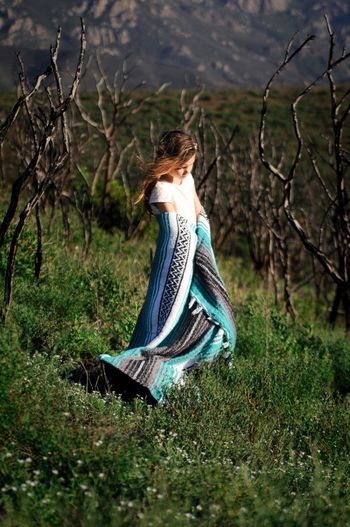Full length of girl with blanket standing on field