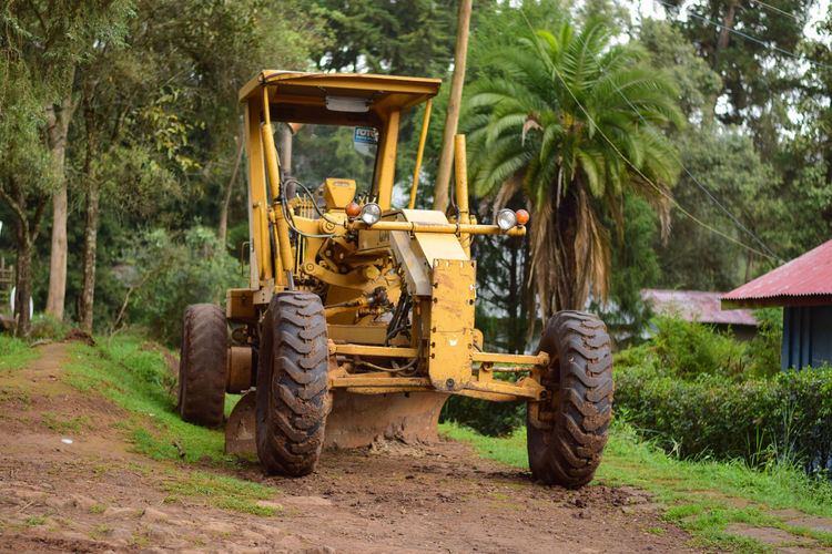 Construction Agricultural Equipment Agricultural Machinery Bulldozer Construction Equipment Construction Industry Construction Machinery Day Dirt Earth Mover Field Forest Land Land Vehicle Machinery Mode Of Transportation Nature Outdoors Plant Road Tractor Transportation Tree Wheel