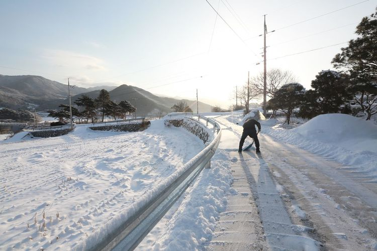 Rear view of man cleaning snow on road