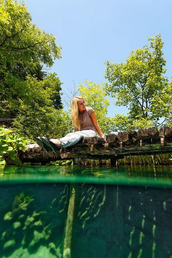 Woman relaxing in swimming pool against lake