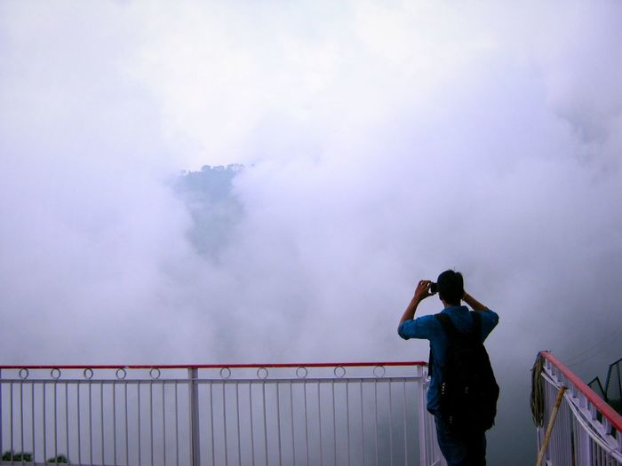 Rear view of young man photographing cloudy sky