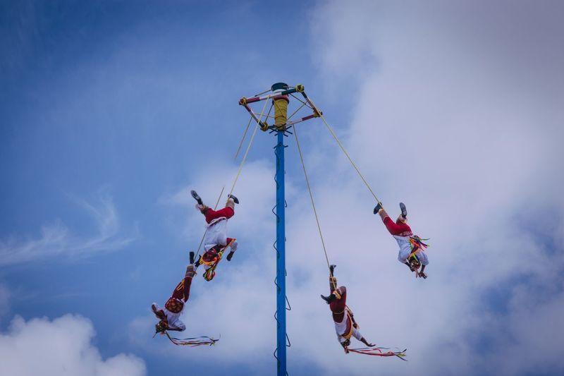 Low angle view of people hanging against sky