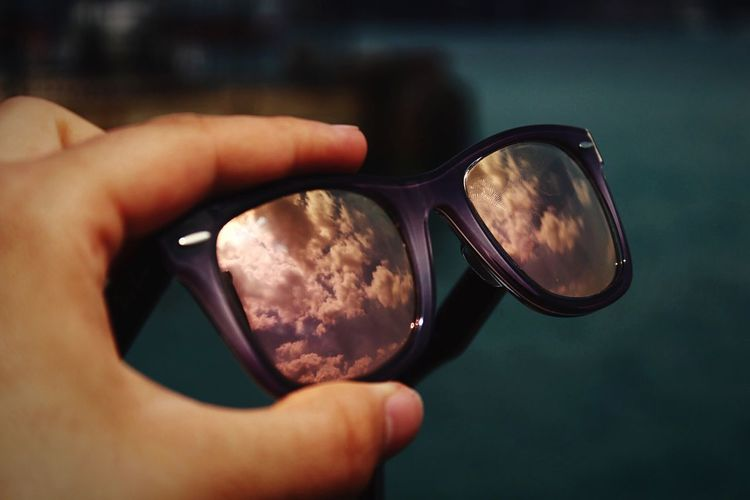 Cropped hand of person holding sunglasses