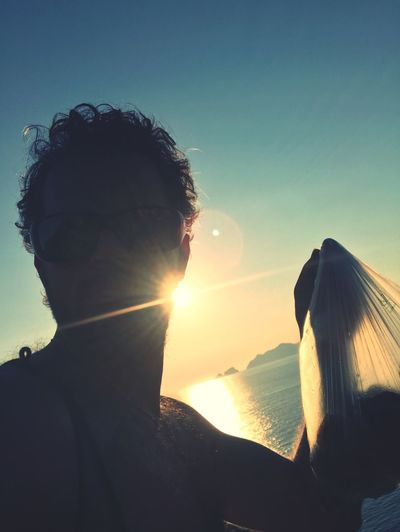 Close-up of man holding bag against sea during sunset