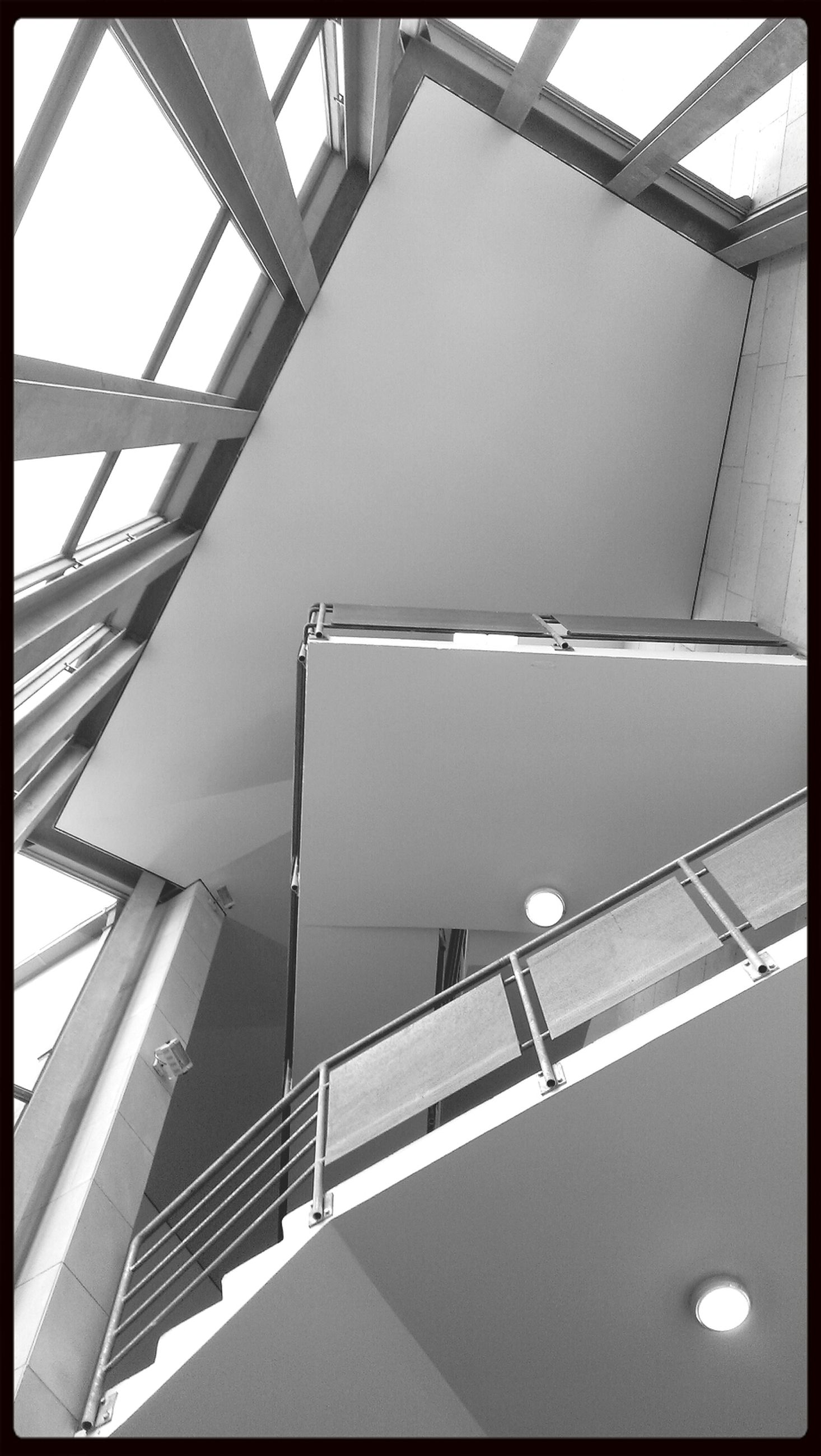 low angle view, architecture, built structure, building exterior, modern, directly below, building, railing, indoors, transfer print, ceiling, auto post production filter, office building, city, staircase, no people, sky, day, clear sky, glass - material