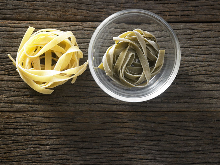 tagliatelle pasta on the wooden table Container Dried Food Food And Drink Spaghetti Tagliatelle Bowl Carbohydrate - Food Type Close-up Directly Above Fettuccine Food Freshness Glass - Material Healthy Eating High Angle View Indoors  Italian Food No People Pasta Raw Food Still Life Table Top View Wood - Material Yellow