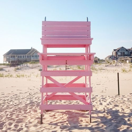 Pink lifeguard chair on sand at beach against clear sky