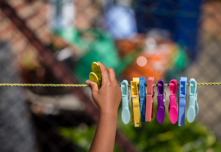 Cropped image of hand pinning clothespin on clothesline