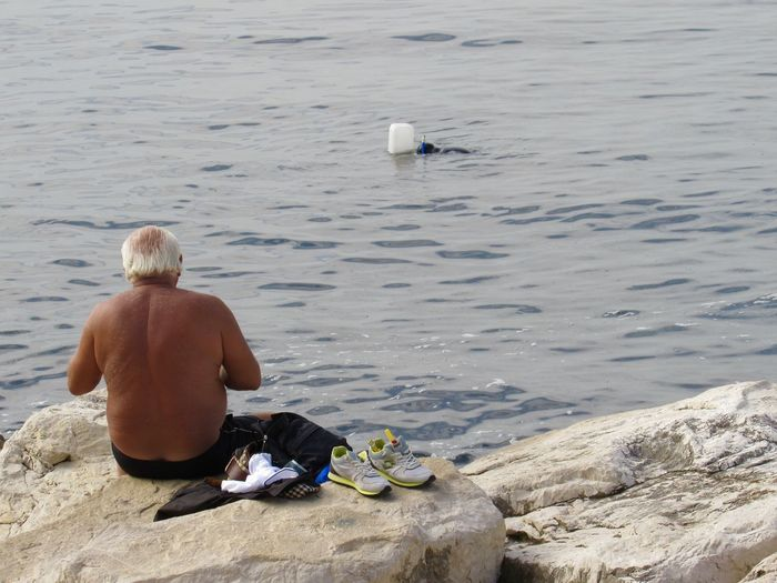 Rear view of shirtless man sitting at beach