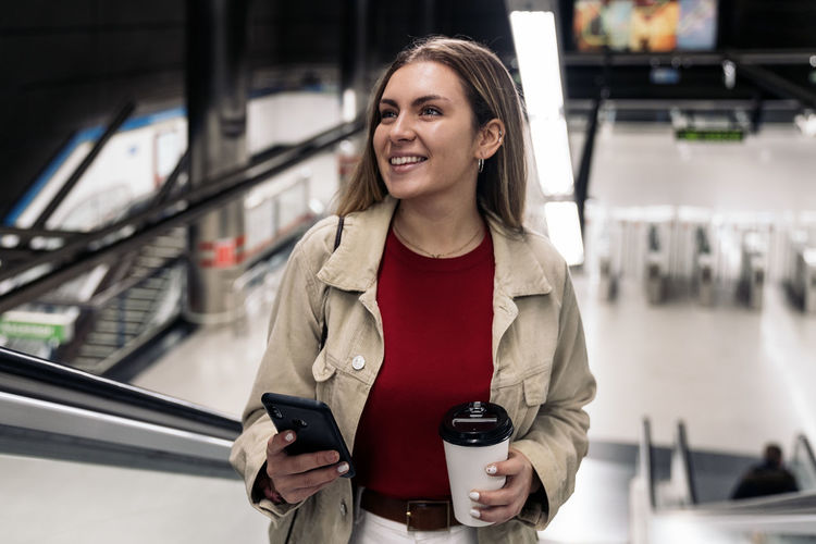 Smiling young woman using mobile phone while standing in bus