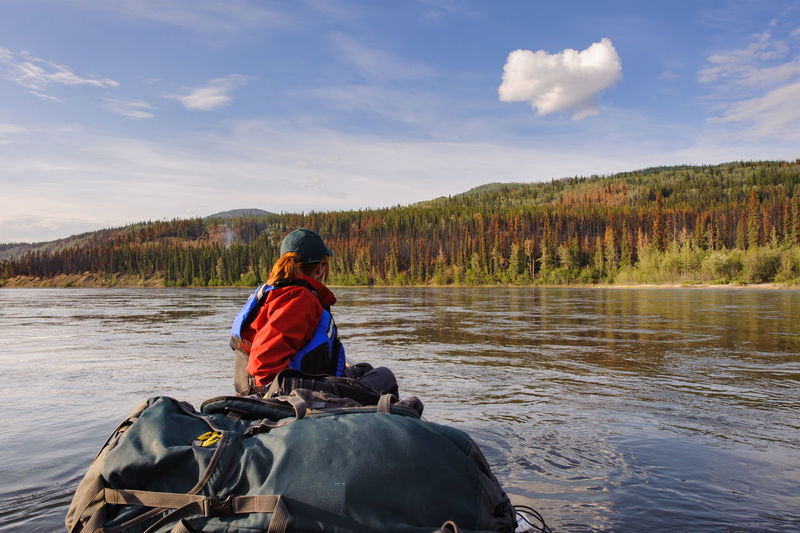 Side view of hiker canoeing on river against cloudy sky at forest