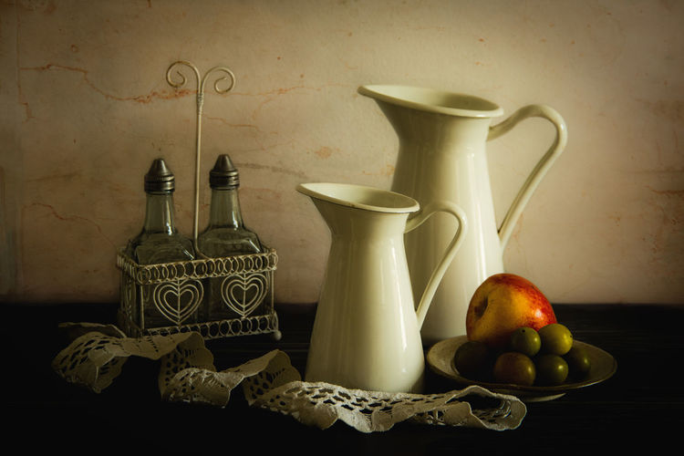 Fruits in jar on table against wall