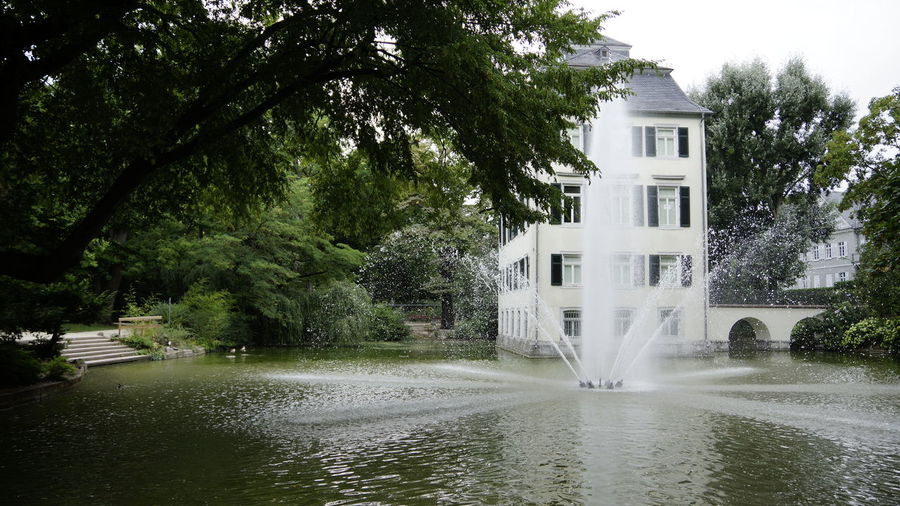 Tree Water Plant Architecture Built Structure Building Exterior Nature Waterfront Growth Building No People Day Motion Lake Outdoors Beauty In Nature House Residential District Spraying Flowing Water Flowing Popular Places