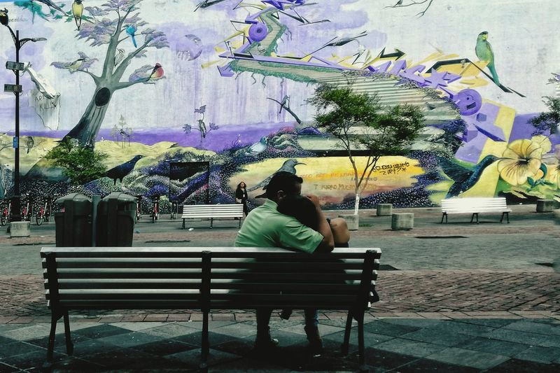 Rear view of a woman sitting on bench