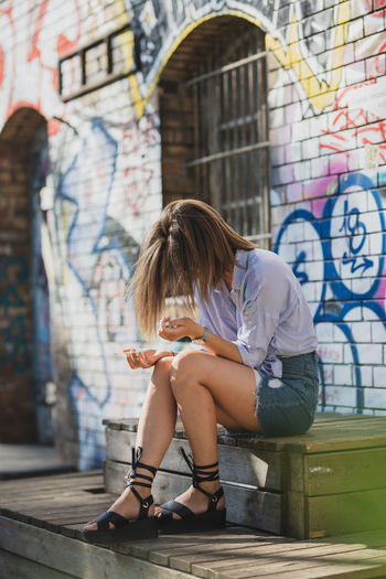 Young woman holding compact disc while sitting on seat against graffiti wall
