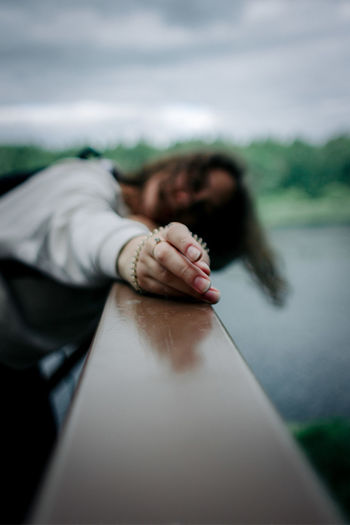 Defocused image of woman relaxing on railing against sky