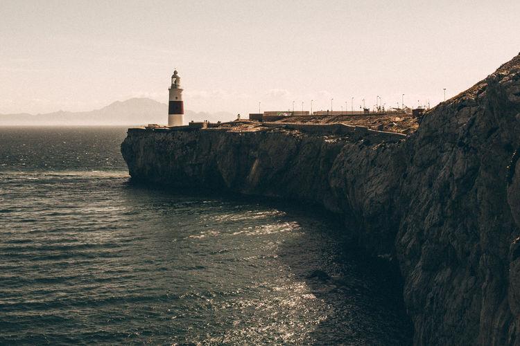 Lighthouse on cliff over sea against sky