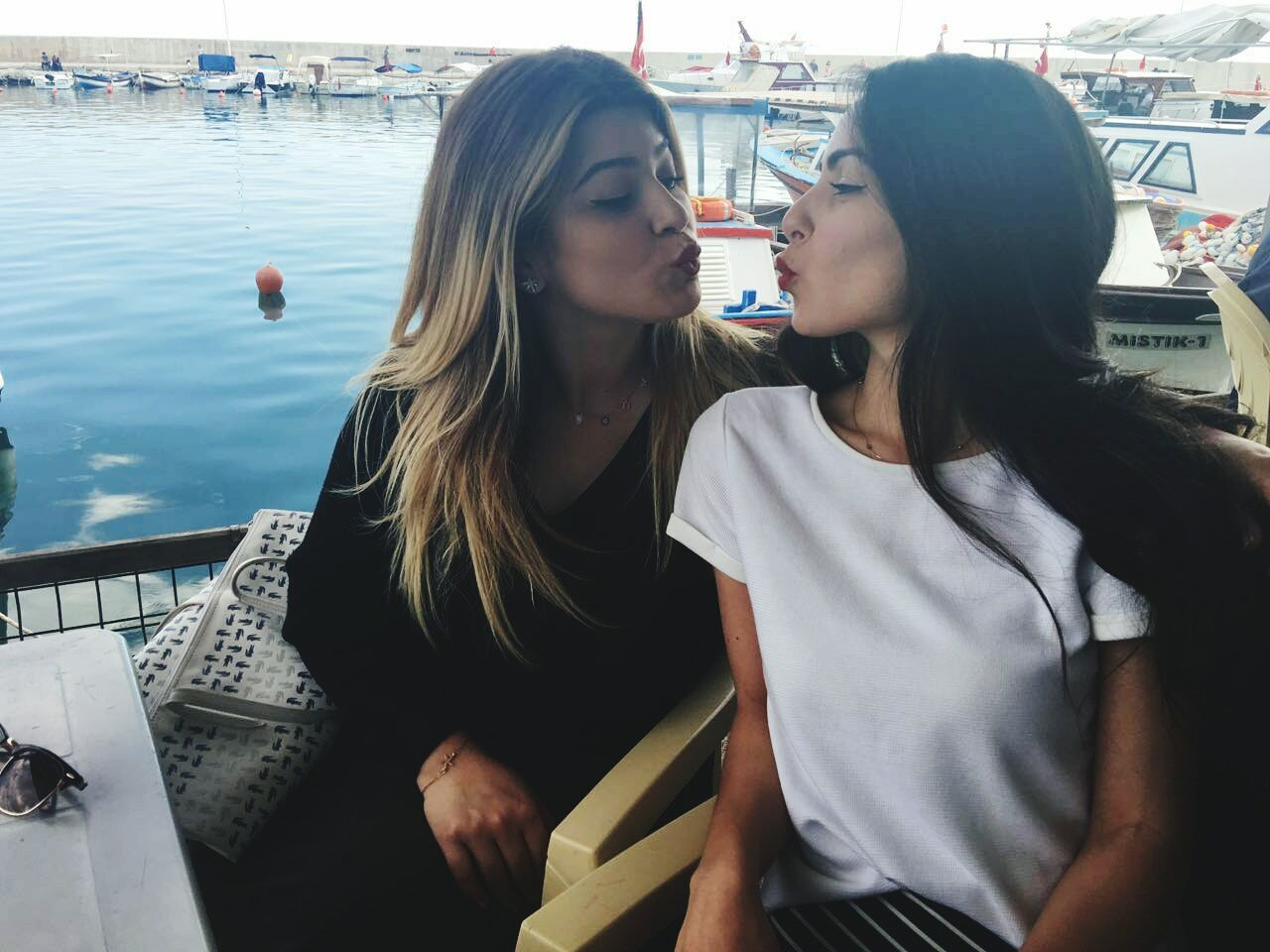 two people, togetherness, young women, young adult, real people, leisure activity, love, casual clothing, bonding, holding, day, lifestyles, sitting, women, friendship, nautical vessel, outdoors, water