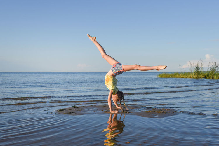 Full length of woman jumping in sea against clear sky