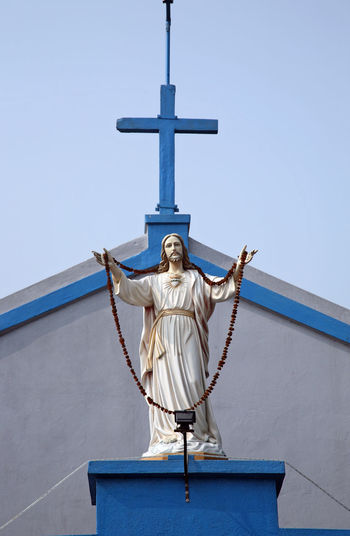 Low Angle View Of Jesus Christ Statue By Church Against Sky