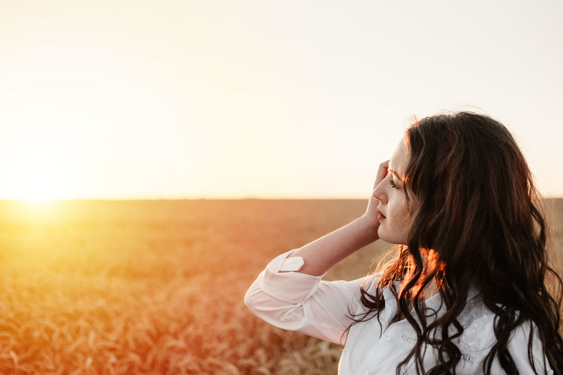 Beautiful woman standing on land against clear sky during sunset
