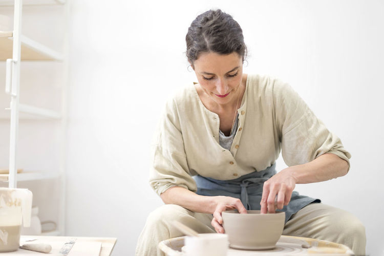 Mid Adult Potter Holding Bowl While Sitting In Workshop
