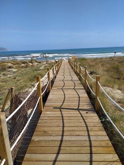 Boardwalk leading towards beach against sky